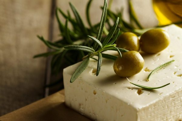 Fresh tasty greek green olives with cheese feta or goat cheese. Closeup. Mediterranean food.Horizontal.