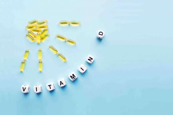 Yellow capsules in the form of the sun with rays and the word vitamin D from white cubes with letters on a blue background. VITAMIN D word for healthy and medical concept. Sunshine vitamin health benefits