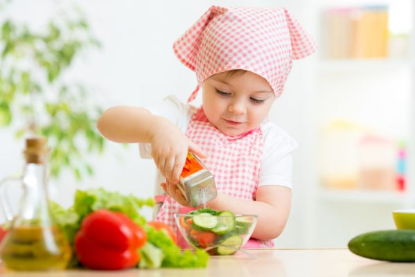 33875071 - cute kid girl preparing vegetables at kitchen
