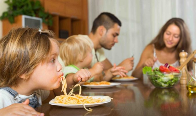 Happy family with playful little daughters eating with spaghetti at table. Focus on girl