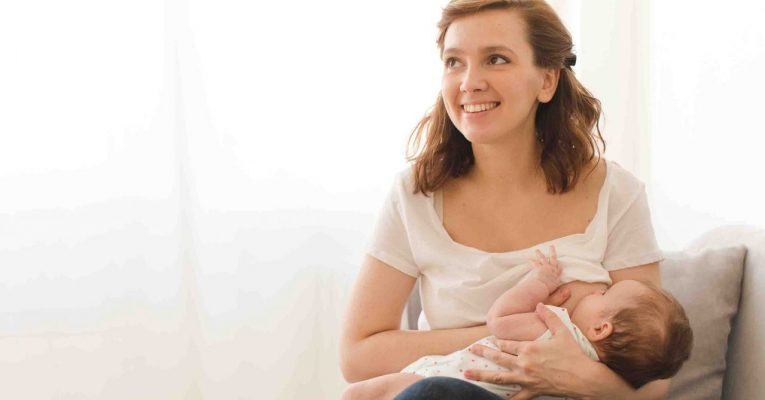 Cheerful young woman breastfeeding infant child at home.