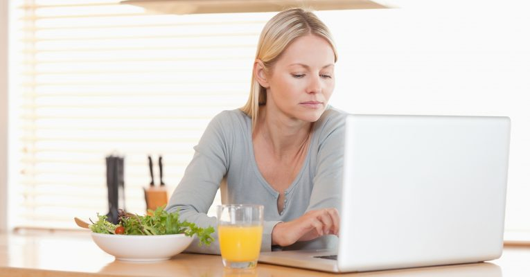 Young woman with salad and orange working on laptop in the kitchen