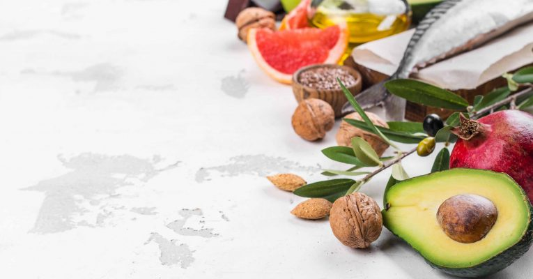 Selection of foods for healthy and strong heart and blood system on white stone background. Copy space